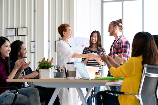 Attractive mature asian woman shaking hand with young beard hipster caucasian with welcome new employee, congratulating successful or happy with business deal while team applauding support together. 1060963192
