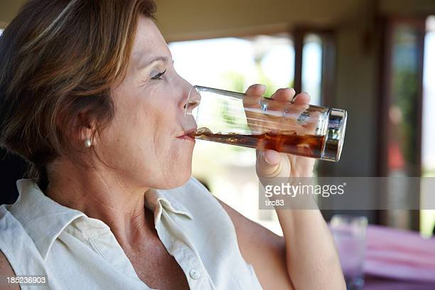 Attractive mature woman drinking soda