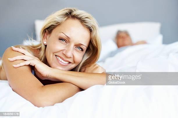 Atractiva mujer madura sonriendo en la cama