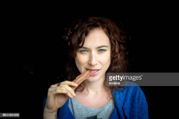 Attractive mature woman wearing casual clothes eating handmade chocolate. Chocolatier holding handmade artisan chocolate piece.