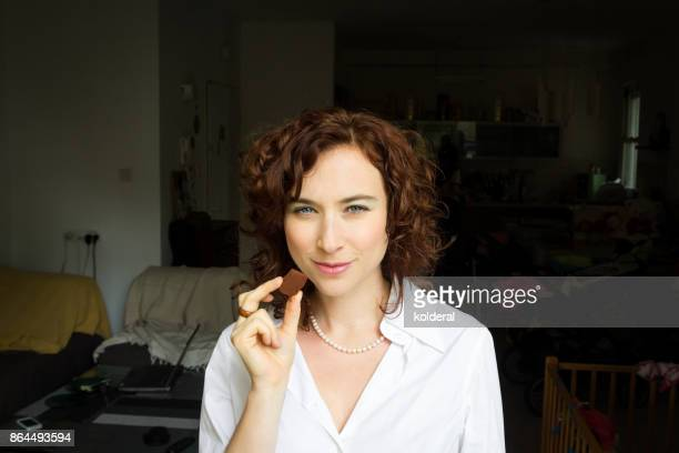 Attractive mature woman wearing white collar shirt eating handmade chocolate at home apartment. Chocolatier holding handmade artisan chocolate truffle.