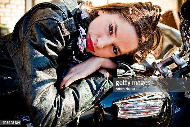 Attractive mid adult woman leaning on motorbike