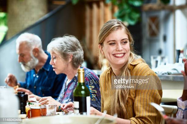 attractive mid adult woman smiling at dinner party - gast stock-fotos und bilder