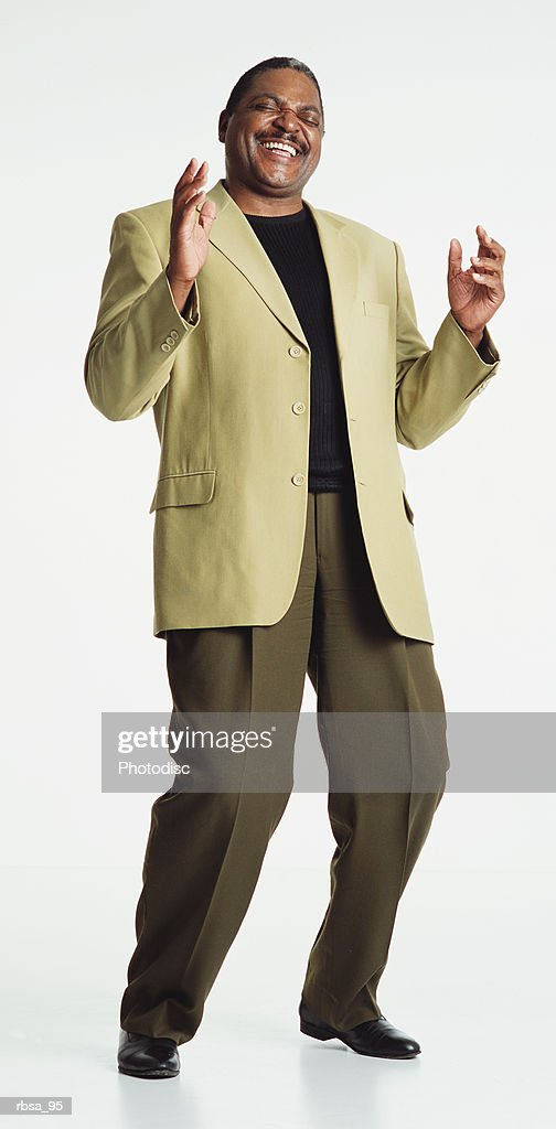attractive middle aged african american adult male with a moustache wearing an olive green blazer and dark shirt and dark olive pants stands in a laughing posture with knees bent and head thrown back slightly as he brings his hands forward as if to c : Foto de stock