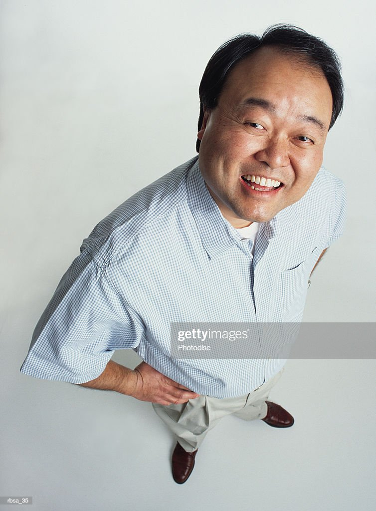 attractive middle aged asian adult male wearing slacks and a light blue shirt stands smiling up at the camera : Foto de stock