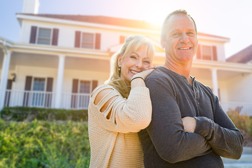 Attractive Middle-aged Couple In Front Of Their House 1143802912