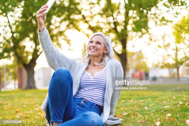 attractive millennial female outdoors in park setting using smart phone photo series - eyecrave  stock pictures, royalty-free photos & images