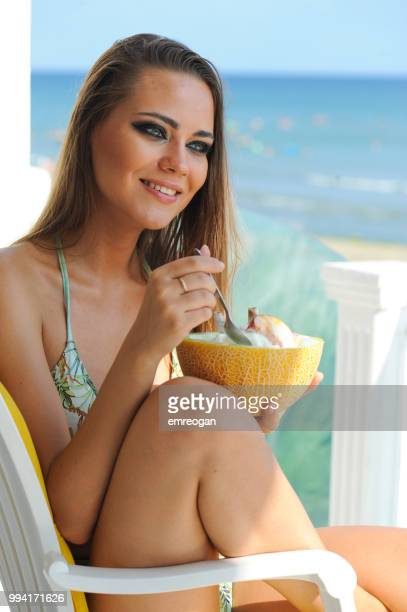 Attractive model resting and eating a fruits