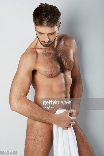 attractive naked hairy man holding bath towel covering looking down - hairy chest stockfoto's en -beelden