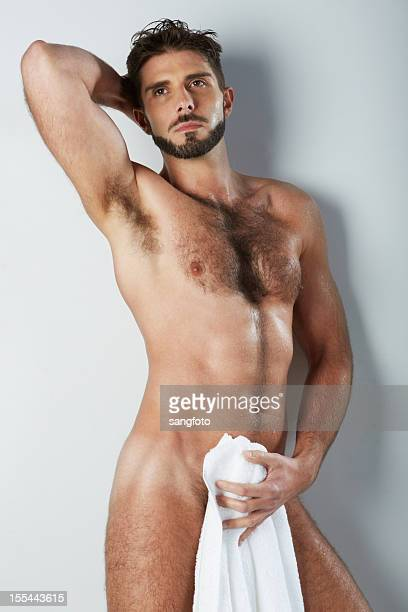 attractive naked hairy man holding bath towel covering looking up - hairy chest stock photos and pictures