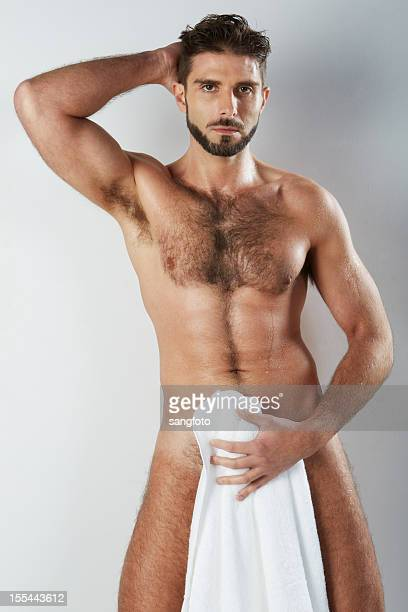 attractive naked hairy man holding bath towel covering - hairy chest stockfoto's en -beelden