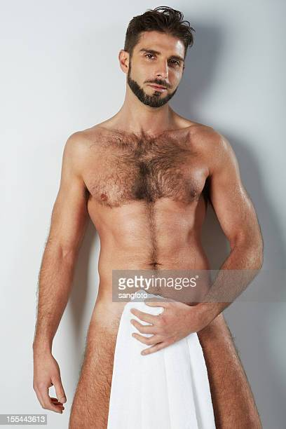Attractive naked hairy man holding bath towel covering smiling