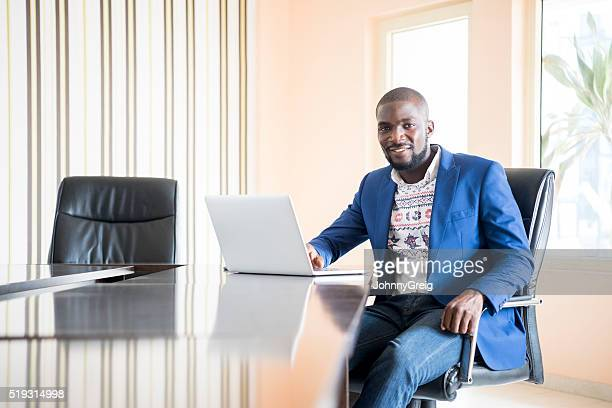 Attractive Nigerian office worker in office using laptop
