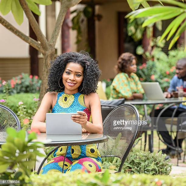 Attractive Nigerian woman sitting at table with tablet
