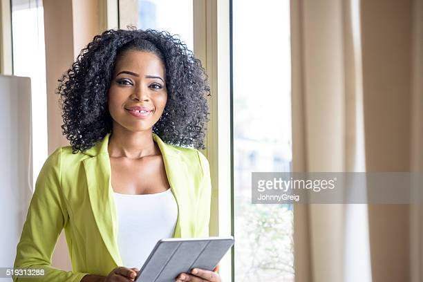 Attractive Nigerian woman with tablet looking at camera