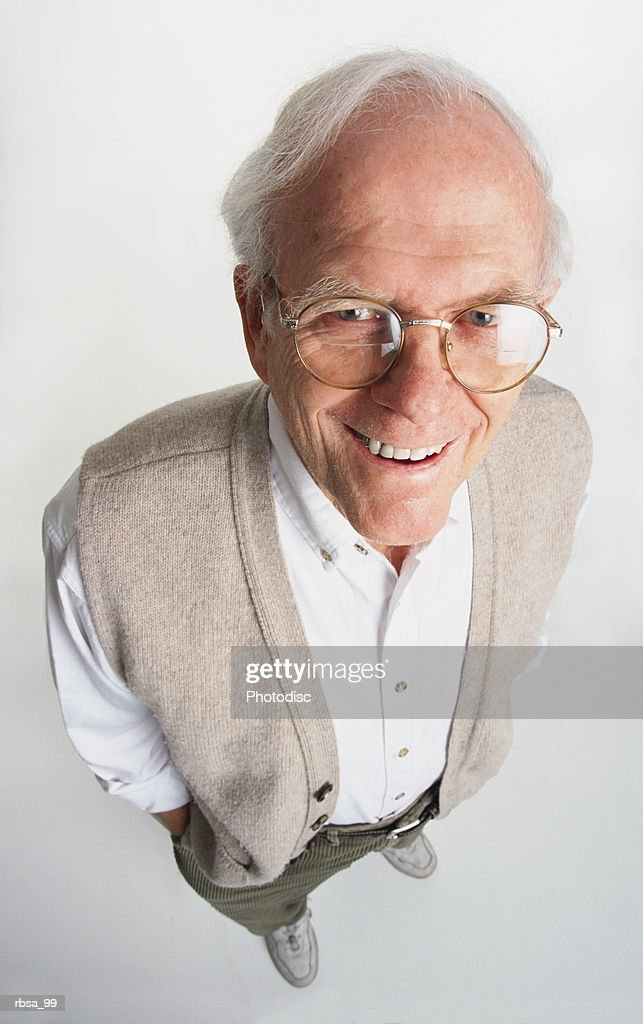 attractive old adult male caucasian with white hair and glasses wearing a tan vest and white shirt stands while looking up at the camera with a kind smile : Foto de stock