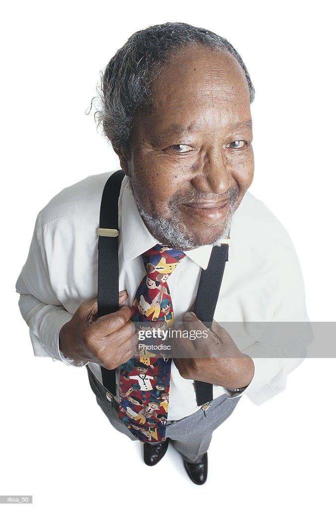 attractive old african american adult male with facial hair and balding gray hair wearing a white dress shirt and a humorous tie and suspenders stands looking up at the camera with his hands on his chest holding his suspenders while smiling : Foto de stock