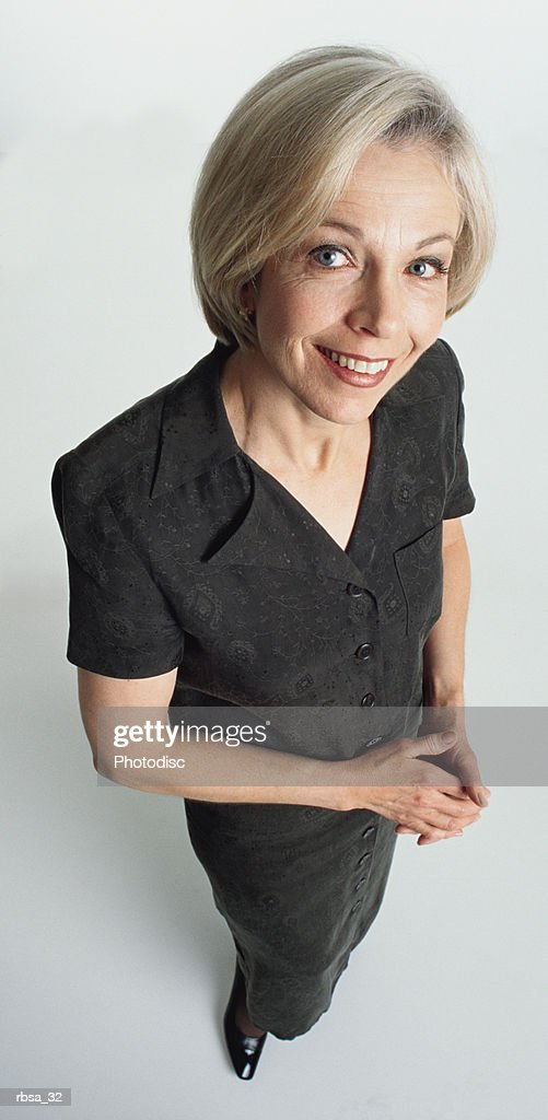 attractive old caucasian adult female dressed stylishly in a dark dress stands sidelong while looking up at the camera confidently : Foto de stock