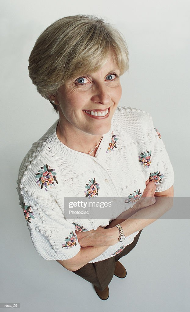 attractive old caucasian adult female with blue eyes wearing a floral sweater stands looking up at the camera smiling approvingly : Foto de stock