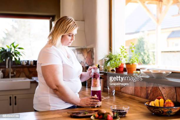 attractive overweight blonde woman in white t-shirt at home preparing a delicious healthy smoothie in her kitchen. - fat nutrient stock pictures, royalty-free photos & images