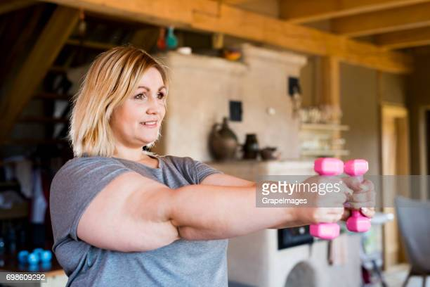 attractive overweight woman at home holding dumbbells, working out. - big fat women stock pictures, royalty-free photos & images