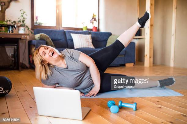 attractive overweight woman at home, laptop in front of her, working out on mat according to video, lifting leg, laughing. - chubby legs stock photos and pictures