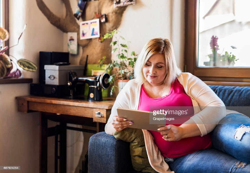 Attractive overweight woman at home sitting on couch working on tablet. : Stock Photo