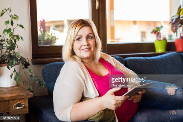 attractive overweight woman at home sitting on couch working on tablet. - fat blonde women stock photos and pictures