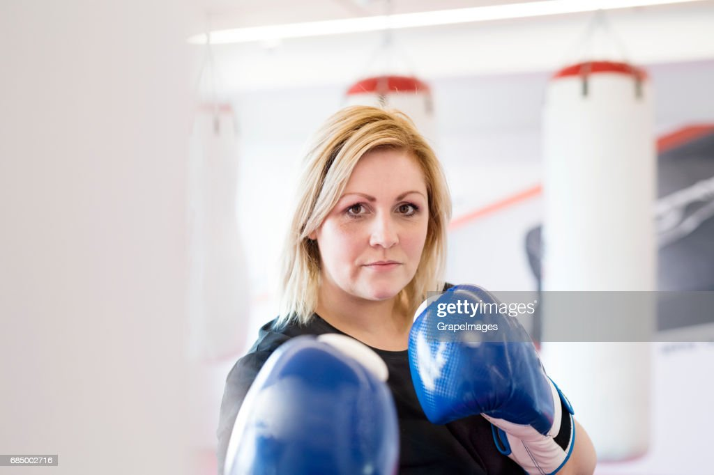 Attractive overweight woman in gym with boxing gloves on. : Stock Photo