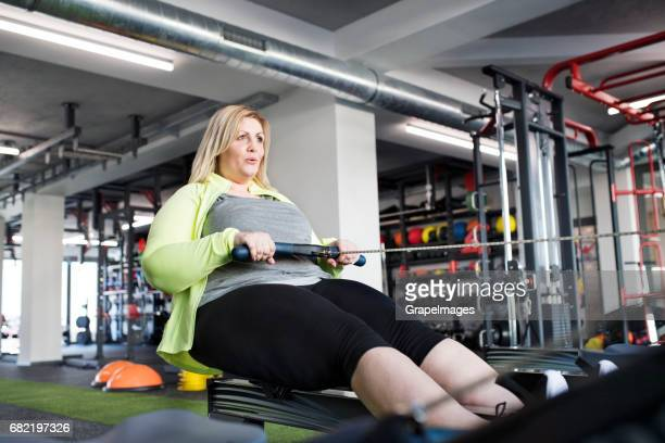 Attractive overweight woman in modern gym exercising on rowing machine.