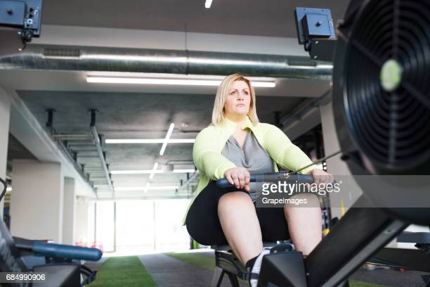 jolie femme en surpoids dans la salle de sport moderne exercice sur machine à ramer. - big fat white women photos et images de collection