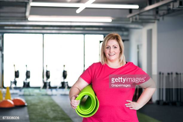 attractive overweight woman in modern gym holding big medicine ball. - fat blonde women stock photos and pictures
