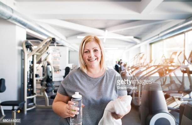 Attractive overweight woman in modern gym resting, drinking water.