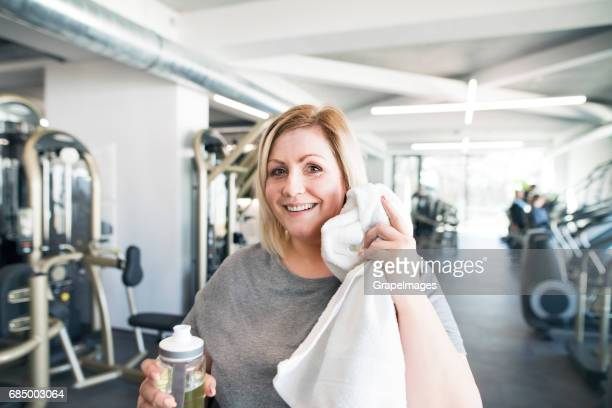 attractive overweight woman in modern gym resting, drinking water. - big fat white women stock pictures, royalty-free photos & images