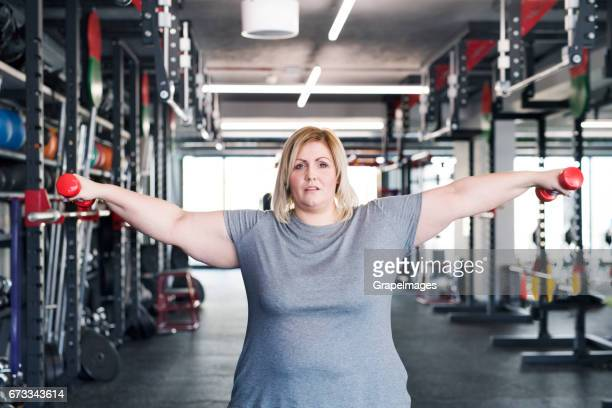 attractive overweight woman in modern gym working out with barbells. - big fat white women stock pictures, royalty-free photos & images