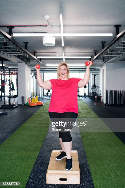 attractive overweight woman in modern gym working out with dumbbells. - big fat white women stock pictures, royalty-free photos & images