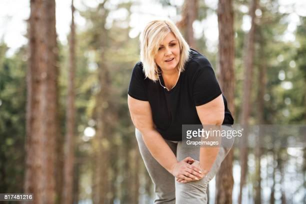 attraktive übergewichtige frau im park ausruhen, aufwärmen oder abkühlen nach einem lauf. - blond mollig frau stock-fotos und bilder