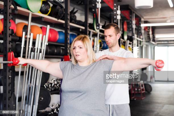 attractive overweight woman with her personal trainer in modern gym working out with dumbbells. - man with big balls stock photos and pictures