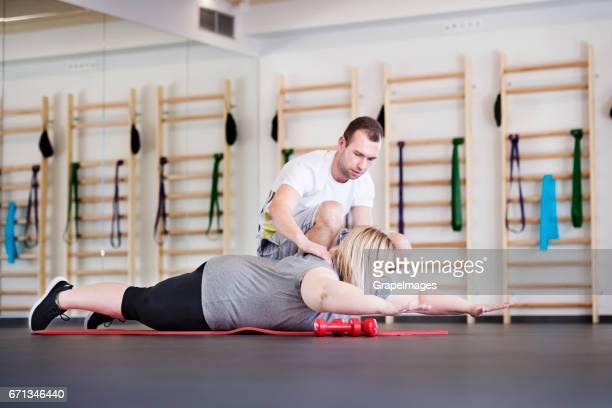 Attraktive übergewichtige Frau mit ihrem persönlichen Trainer im modernen Fitnessraum trainieren auf Matte
