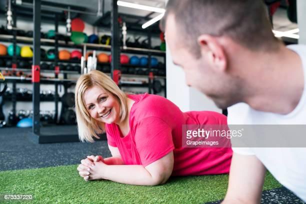 Attraktive übergewichtige Frau mit ihrem persönlichen Trainer im modernen Fitnessraum auf dem Boden liegend
