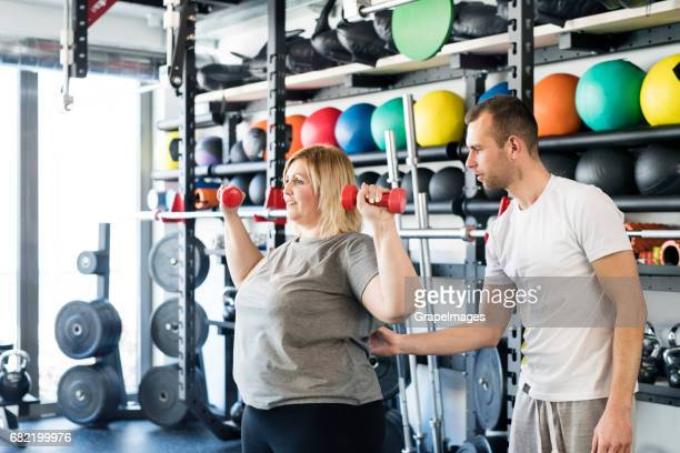 Attractive overweight woman with her personal trainer in modern gym working out with dumbbells.