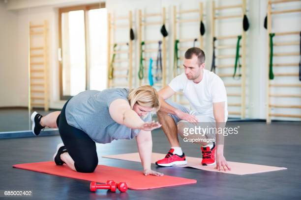 attractive overweight woman with her personal trainer in modern gym working out on mat - big fat white women stock pictures, royalty-free photos & images