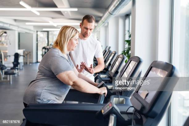 attractive overweight woman with her personal trainer running on treadmill in modern gym. - big fat white women stock pictures, royalty-free photos & images