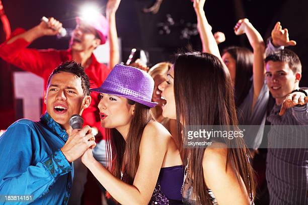 Attractive people on a karaoke party in discotheque.