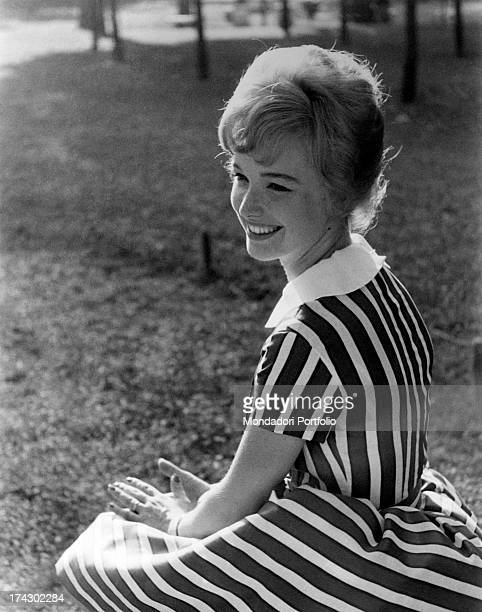 Attractive portrait of announcer Aba Cercato smiling she is nestled on the grass wearing a refined striped dress June 1960