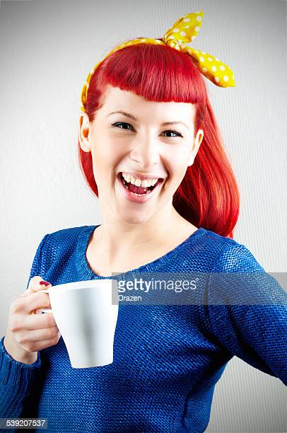 Attractive red head with bow and cup of coffee smiling