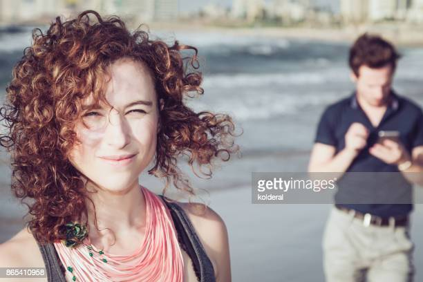 Attractive redhead woman looking at camera on Mediterranean beach