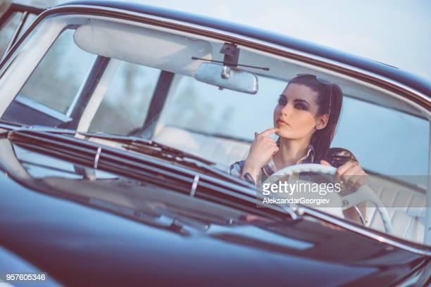 Schöne Retro Frau in alten Stoppuhr-Auto bei Sonnenuntergang