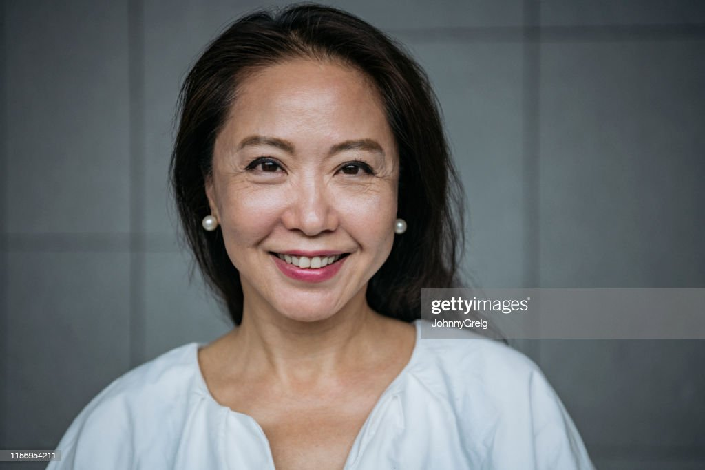 Attractive senior Chinese woman smiling : Stock Photo