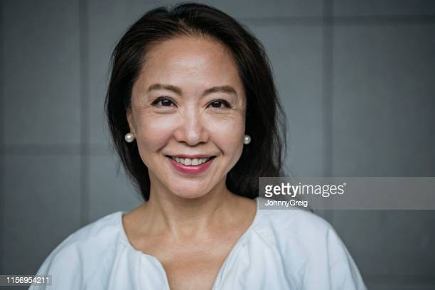 attractive senior chinese woman smiling - only women stock pictures, royalty-free photos & images
